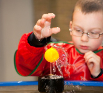 boy playing with water display in splash lab