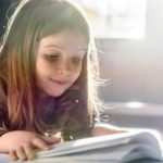 Girl with long hair leaning over a book and reading with a slight smile on her face